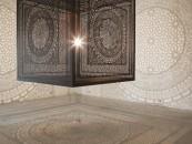 Cub sculptat din lemn care proiecteaza umbre pe peretii galeriei